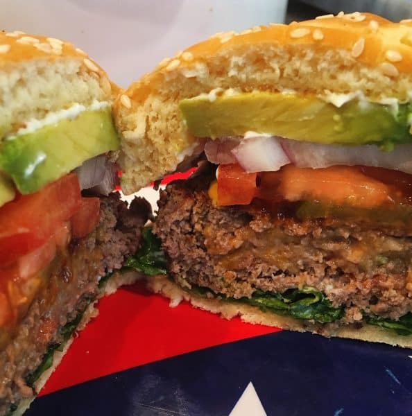 Burger cut in half with cheese and bacon showing
