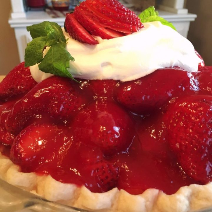 Close-up photo of Strawberry Pie with a dollop of whipped cream and mint