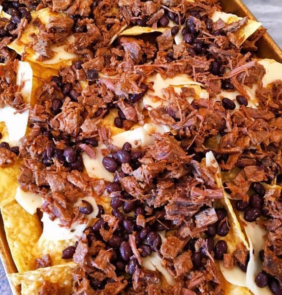 Tortilla chips topped of with cheese, meat, and beans