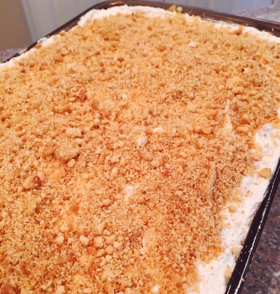 Coconut whipped cream topping spread over orange creamsicle dessert with cookie cream topping.