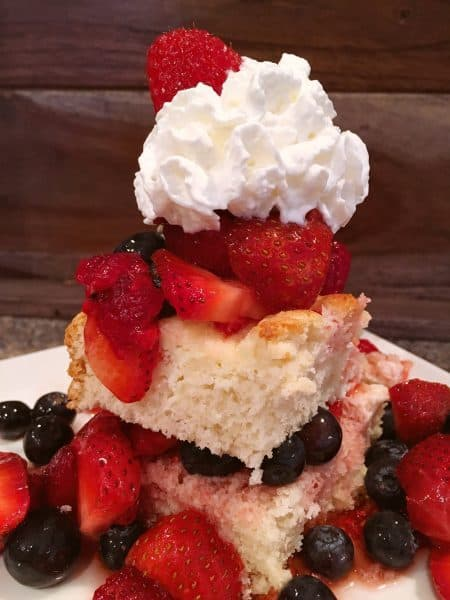slice of cheesecake short bread topped off with fresh triple berries and whipped cream