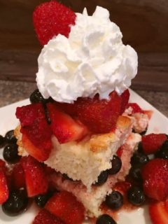 A slice of shortcake made with strawberries, blue berries and raspberries with whipped cream on top