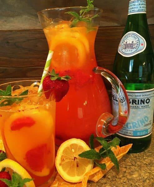 A glass and pitcher of Sparkling Strawberry Mango Lemonade