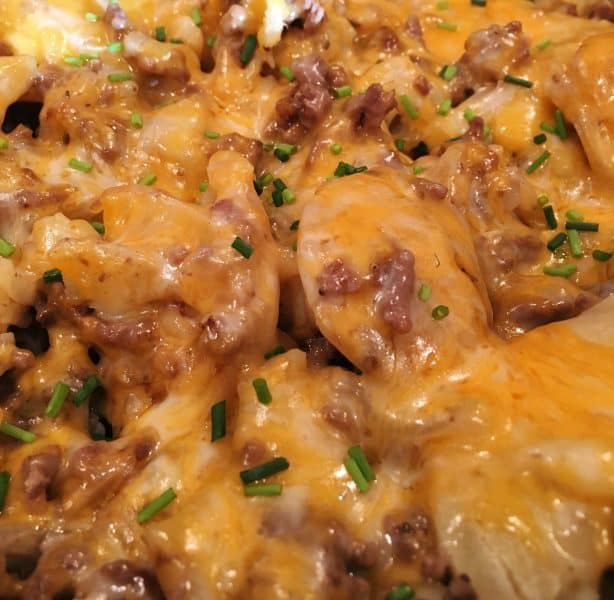 Close up photo of cooked potatoes and hamburger with melted cheese and diced chives.