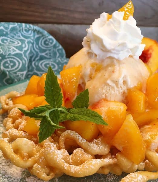 close up of peaches and cream funnel cake