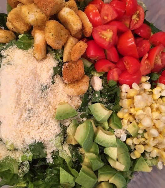 addition of grape tomatoes, avocado, corn, Parmesan cheese, and croutons