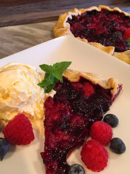 sliced of triple berry galette with vanilla ice cream scoop
