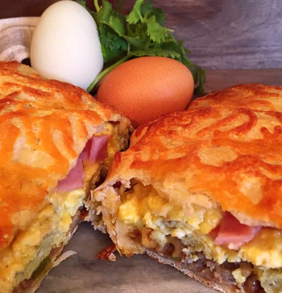 A calzone made with egg, sausage, onion, cheese, and peppers