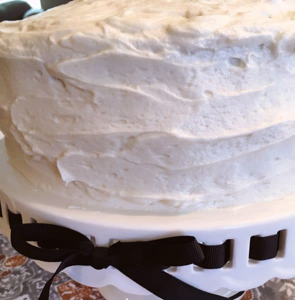 cream cheese frosting on cake on cake plate