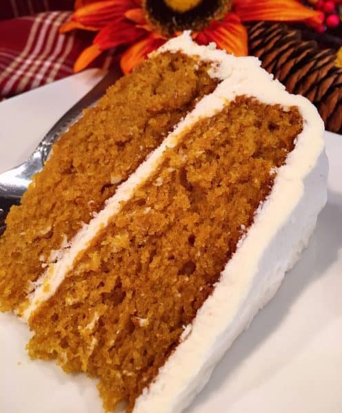 slice of pumpkin cake with cream cheese frosting on white plate