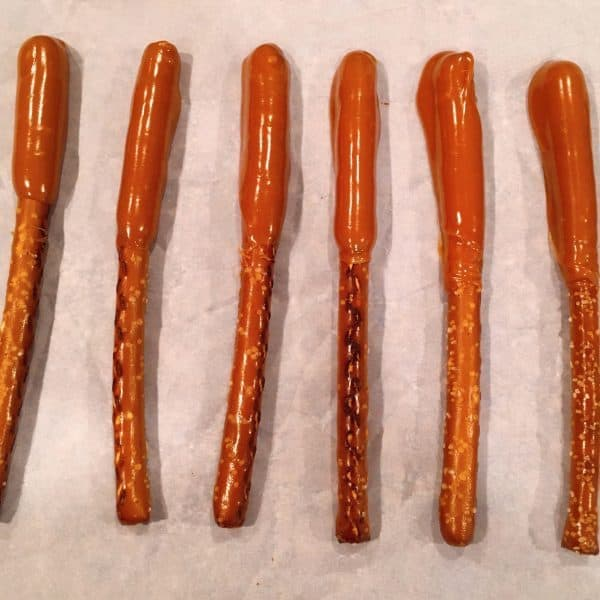 Pretzel Stick dipped in caramel and setting up on parchment paper