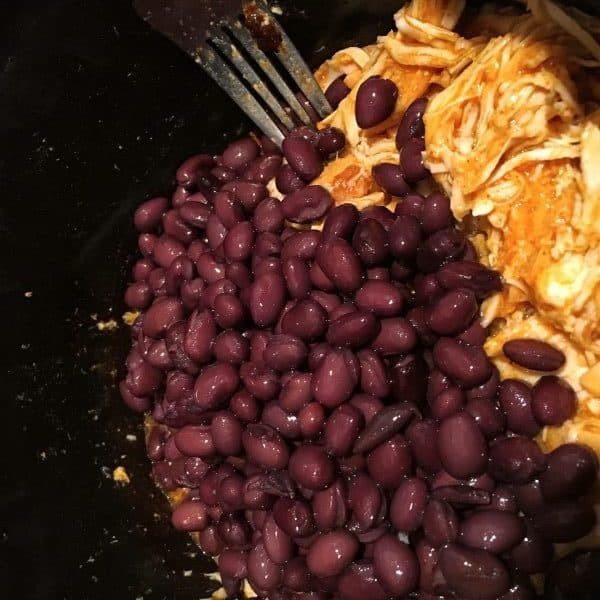 Adding rinsed black beans with shredded taco chicken