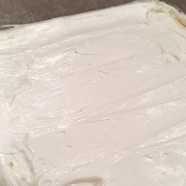 spreading cream cheese layer over crumb crust