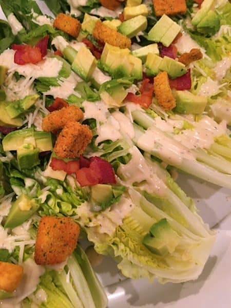 Romaine Lettuce heads cut in half and topped with avocado, cheese, and dressing