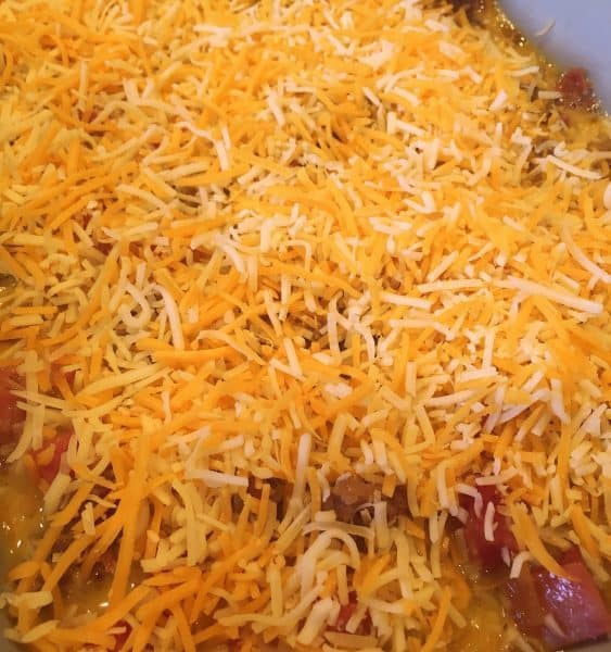 grated cheese on top of egg mixture in casserole dish for breakfast casserole