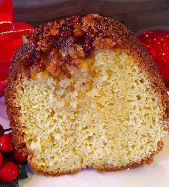 Slice of the Worlds Best Rum Cake topped with delicious pecans