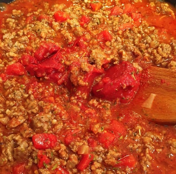 Adding tomato sauce and paste to cooked meat for spaghetti sauce