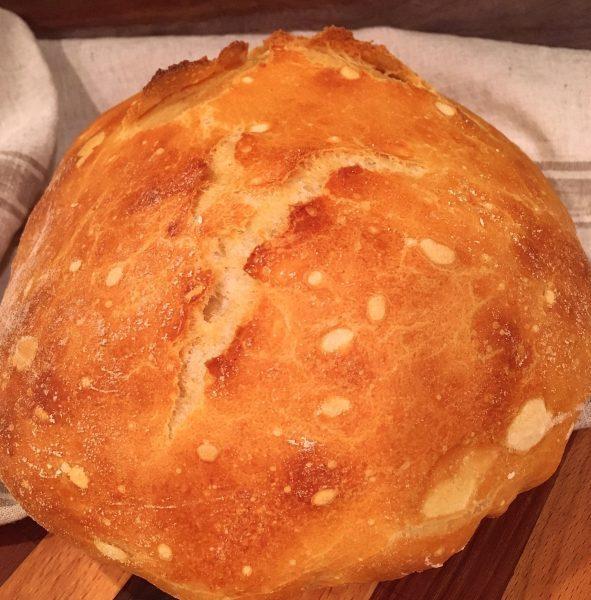 Beautiful golden brown Artisan bread on cutting board
