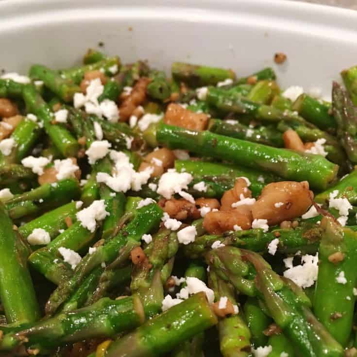 Tender Asparagus spears and walnuts are sauteed in walnut oil and butter and topped with creamy flavorful feta cheese for a truly delicate delicious side dish.