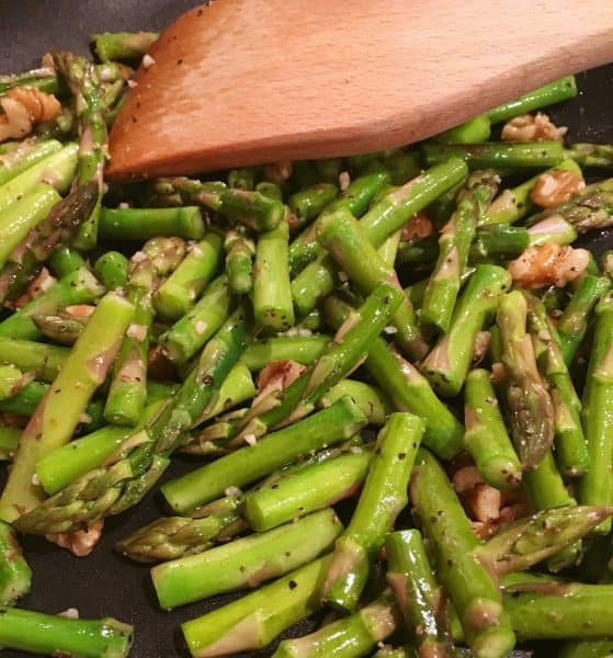 Cut up Asparagus spears sauteed in a skillet with chopped walnuts and seasonsings