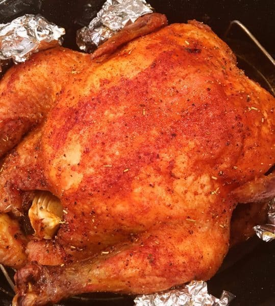 Whole slow roasted chicken in roasting pan coming out of the oven