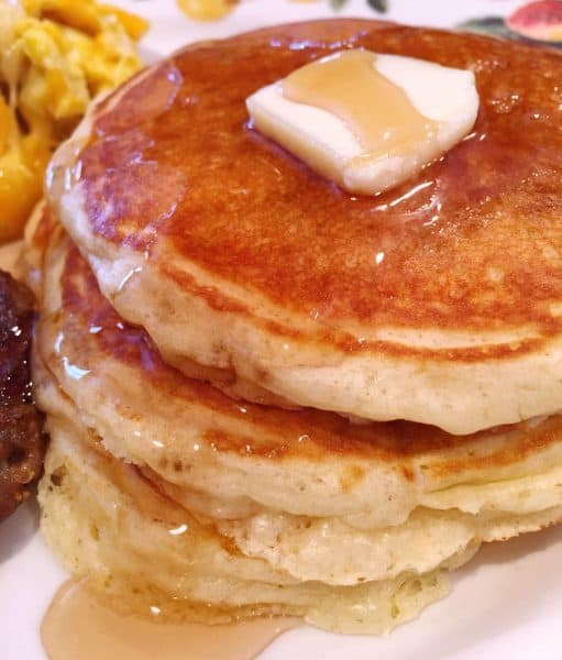 Plate piled high with light fluffy buttermilk pancakes topped with rich maple syrup