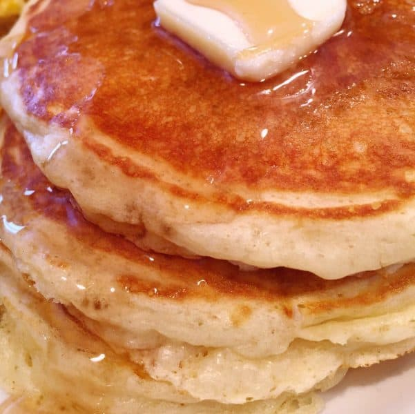 Stack of Fluffy Buttermilk Pancakes with a pat of butter and rich maple syrup