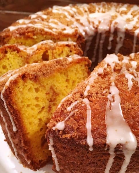 Round Bundt Cake with slices leaning on cinnamon coffee cake drizzled with vanilla icing.