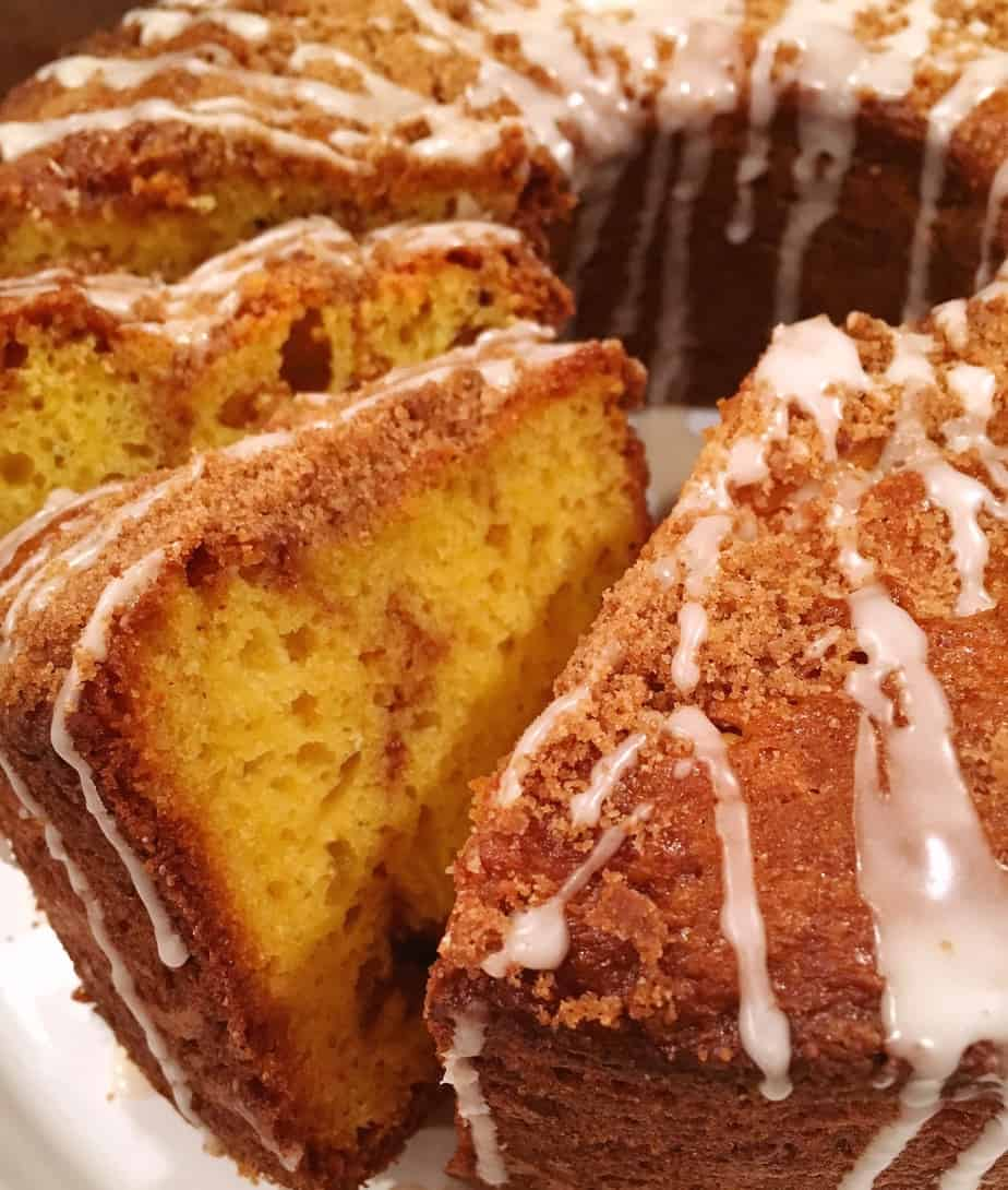 Large bundt yellow cake with swirls of cinnamon filling and a light streusel crumb topping and drizzles of vanilla glaze.