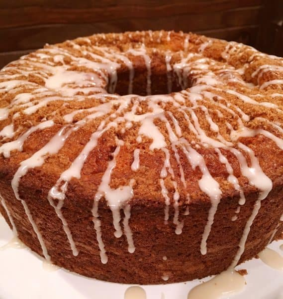 Full Cake Mix Cinnamon Bundt Cake on cake stand with vanilla glaze icing drizzle.