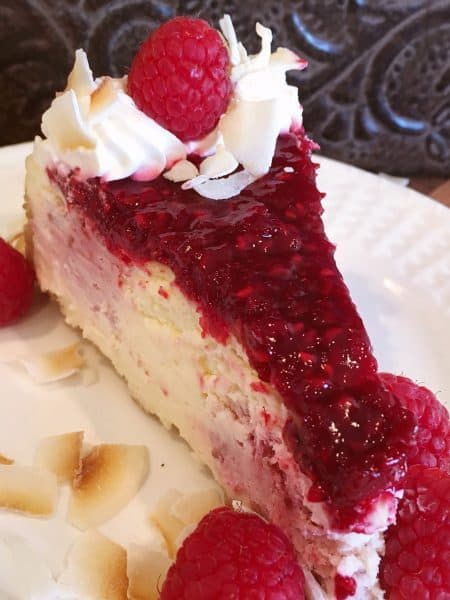 Slice of Coconut Raspberry Cheesecake with beautiful Raspberry swirls