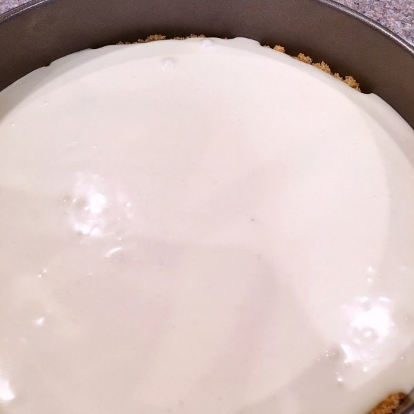 Coconut Cheesecake batter poured into prepared crust in spring form pan for Coconut Raspberry Cheesecake