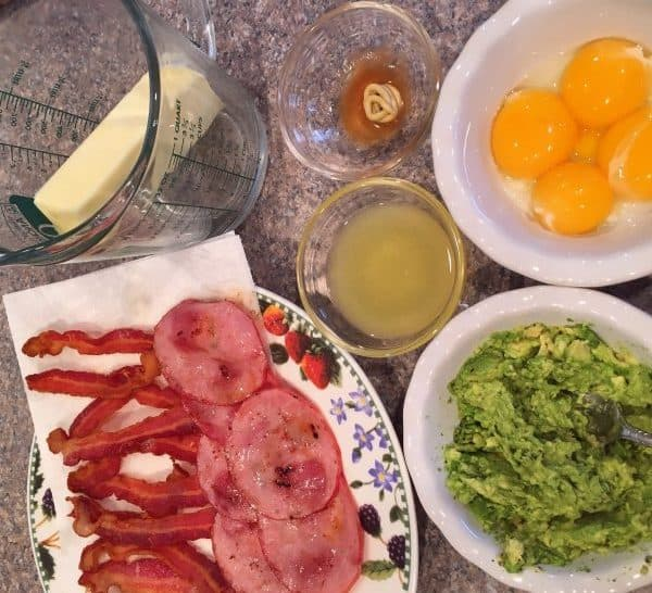 Bowls and plates with Egg Benedict Ingredients, egg yolks, lemon juice, bacon, smashed avocado, butter