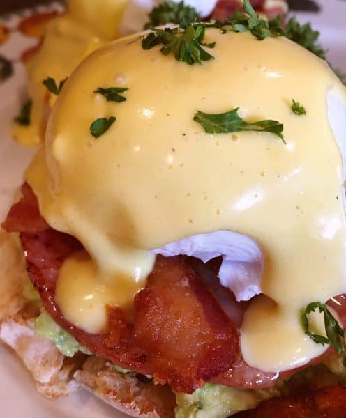 Holandaise sauce poured over Eggs Benedict