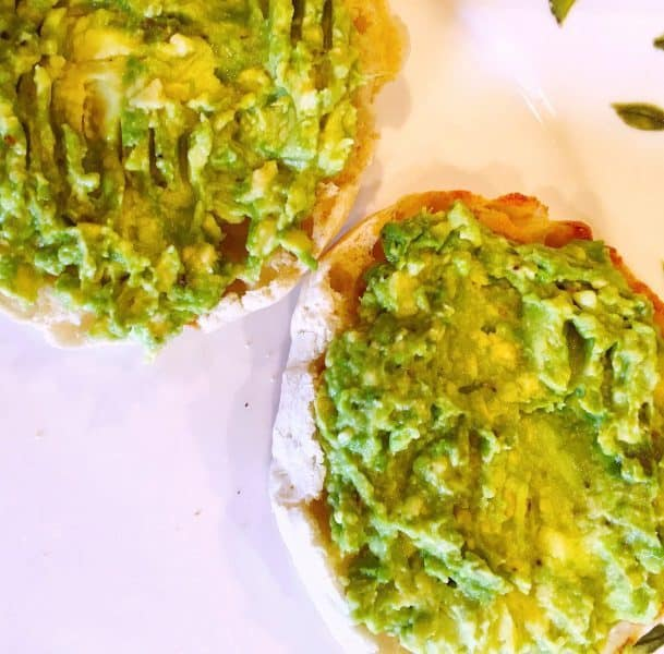 Two slices of English Muffin with smashed avocado