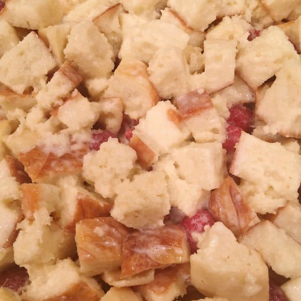 Baking dish with soaked bread cubes and raspberry filling. Topped with remaining bread cubes.