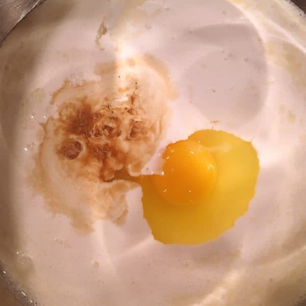 Lage bowl filled with cream, sugar, vanilla, and egg to create batter for bread pudding