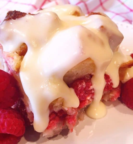A square of Raspberry Bread Pudding Drizzled with Warm Vanilla Cream Sauce.