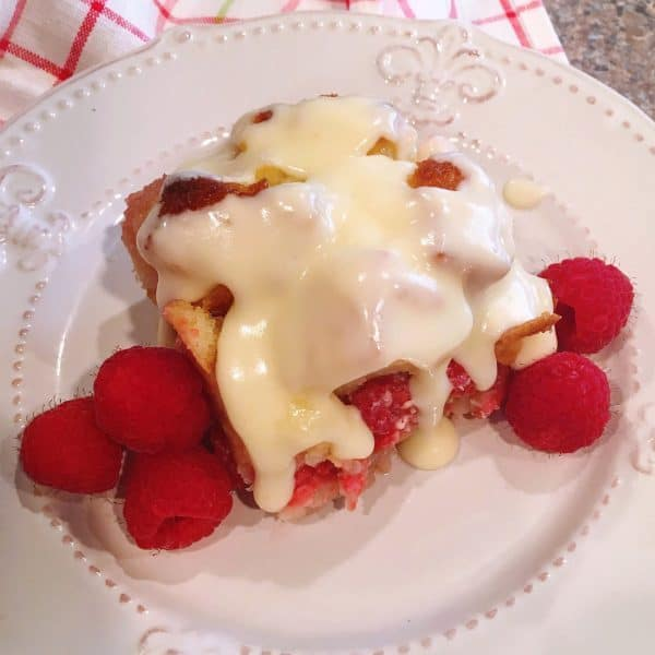 Slice of Raspberry Bread Pudding drizzled with vanilla cream sauce and garnished with fresh raspberries