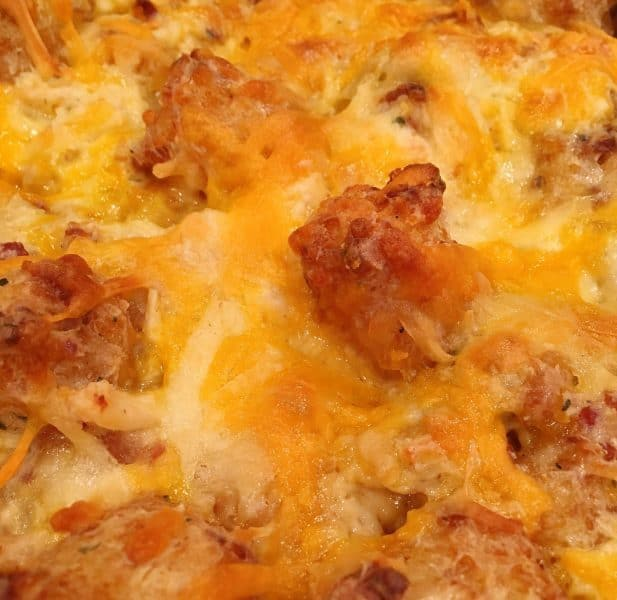 Baked 9 x 13 pan of Chicken Ranch Tater Tot Casserole with melted cheese on top