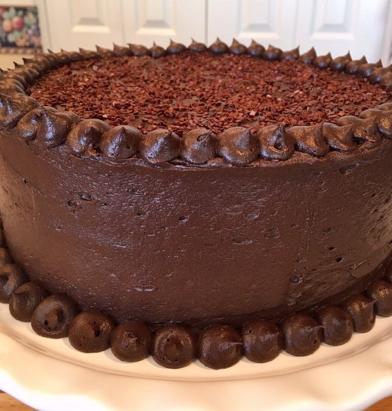 Dark Chocolate Cake decorated on a cake stand