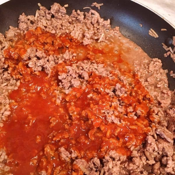 Add enchilada sauce to ground beef