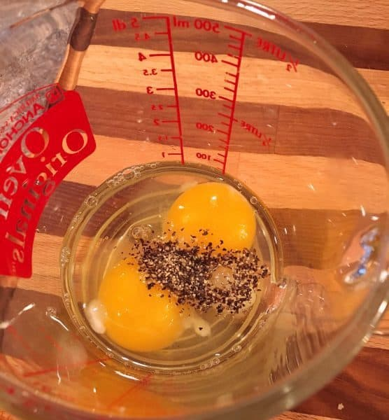 Eggs and seasonings in measuring cup.