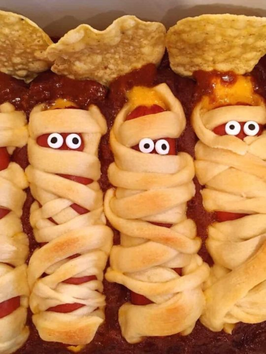 hot dogs wrapped in crescent dough on a bed of chili