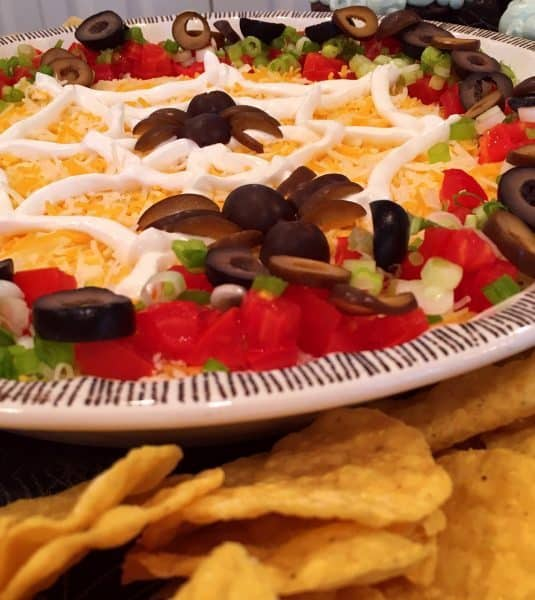 Spooky Halloween Seven Layer Taco Dip with corn chips