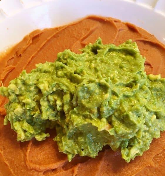 Spread layer of guacamole over bean dip