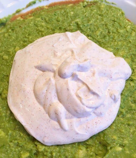 Sour cream taco seasoning mixture on top of guacamole