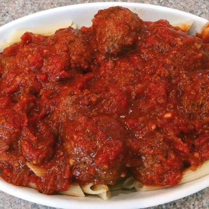 Meatballs and pasta in a baking dish with lots of yummy sauce.