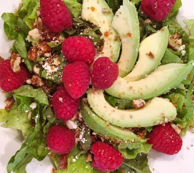 Adding Avocado and Raspberries to salad.