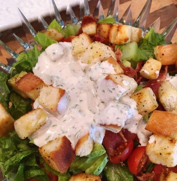 adding creamy dressing to salad